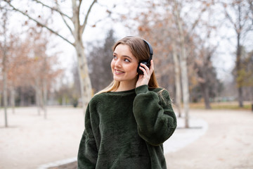 Attractive young female in headphones cheerfully smiling and looking away while walking in autumn park and listening to music