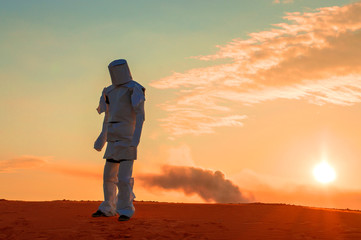 man in the wilderness in a torn spacesuit, goes after the crash of the rocket, amid smoke.