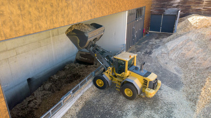 A powerful backhoe loading wood chips into in the tank of a biomsss power plant. Wood chips for biomass heating energy.