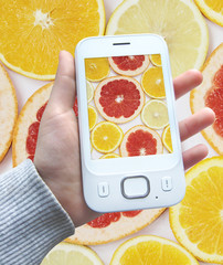 smartphone with image of citrus fruits on screen in hand isolated on white