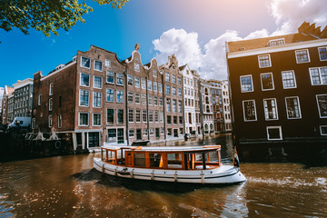 City of Amsterdam in Holland picturesque scenery, white boats on a canal between historic houses