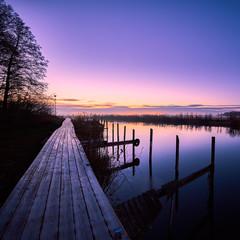 bridge leading along a river at sunrise a winter morning