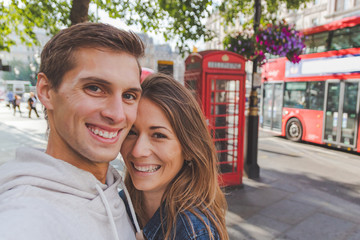 Printed roller blinds London red bus happy young couple taking a selfie in front of a phone box and a red bus in London