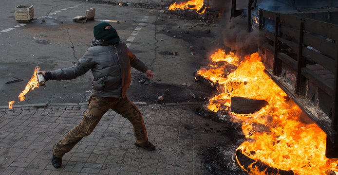 Street Protestant with a Molotov cocktail against a fire