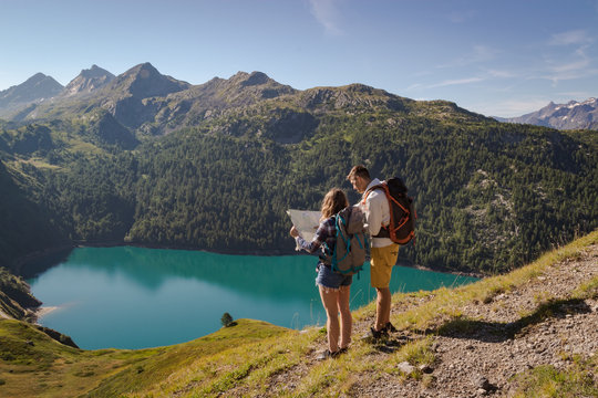 Young couple with backpack reading a map in the swiss alps. Lake ritom as background