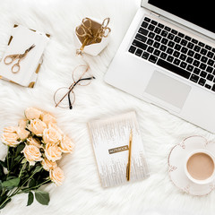 Female workspace with laptop, roses flowers bouquet, golden accessories, notebook, glasses. Flat lay women's office desk. Top view feminine background.