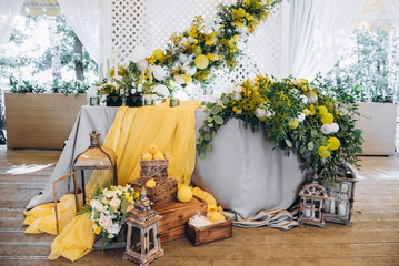 Wedding decorations in yellow color. Wedding presidium for the newlyweds. Beautiful decor of flowers, lemons and candles