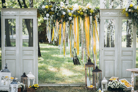 Wedding ceremony. Festive arch. Beautiful wedding decor with many flowers, lemons, balloons and candles. Celebration, outdoors