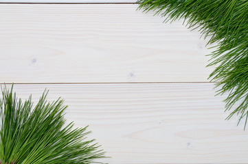 Christmas and New Year tree branches on a white wooden background.