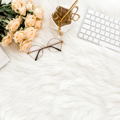 Female workspace with computer, roses flowers bouquet, golden accessories, diary, glasses on white background. Flat lay women's office desk. Top view feminine background.