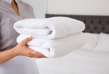 Young chambermaid with clean towels in bedroom, closeup