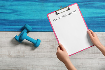 Woman holding clipboard with words HOW TO LOSE WEIGHT over sport equipment, top view