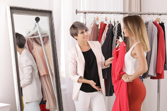 Young stylist helping client to choose trendy clothes in studio