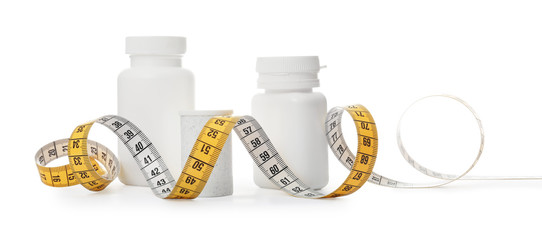 Bottles of weight loss pills and measuring tape isolated on white