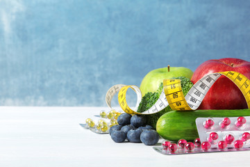 Weight loss pills with measuring tape and healthy food on light table. Space for text