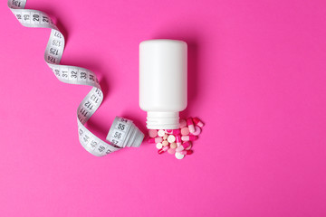 Weight loss pills, bottle and measuring tape on color background, flat lay