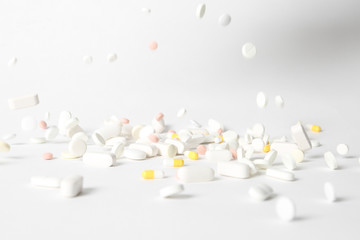 Different pills falling on table against white background