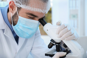 Young scientist working with microscope in laboratory, closeup. Chemical analysis