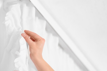 Young woman hanging window curtain in room, closeup. Space for text