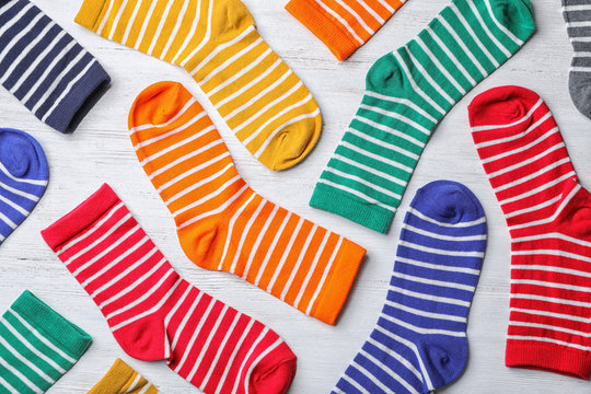 Flat lay composition with cute child socks on white wooden background