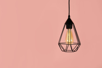 Modern hanging lamp on color background, space for text. Idea for interior design