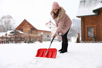Young woman cleaning snow with shovel near her house