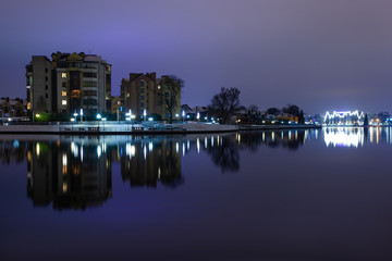 night cityscape near the lake with bright lights