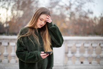 Troubled young woman rubbing forehead and looking at modern smartphone while standing in autumn park