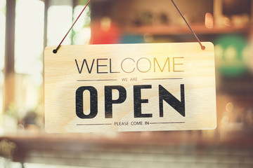 A business sign that says 'Open' on cafe or restaurant hang on door at entrance. Vintage color tone style.