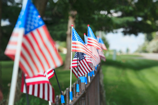 A row of small flags mounted on a metal fence showing one point perspective with green grass and trees in the picture.