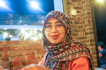Portrait of pretty young asian muslim woman waiting to order at a restaurant. Emotion Expression