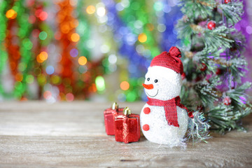Christmas snow man and red gift box and christmas tree with bokeh background on wooden table