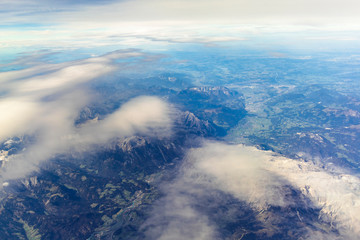 Blue sky and mountain landscape over Europe from an airplane window