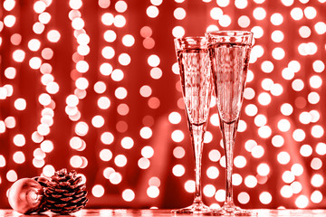 Wall Mural - Two glasses of champagne with Christmas toys. Festive lights bokeh background. Coral accent - color of the year 2019