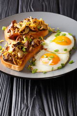Healthy breakfast of toast with shiitake mushrooms and cheddar cheese and fried eggs close-up. vertical