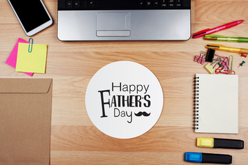 Happy Father's Day card with office supplies on wooden desk