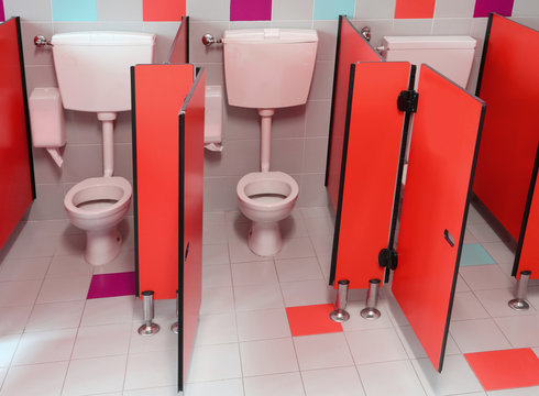 small toilets with red doors for children in a kindergarten