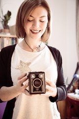Beautiful laughing girl with a vintage film camera