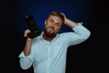 man photographer standing with a camera on a dark background