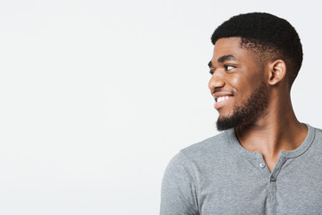 Half-turned smiling african-american man looking at copy space