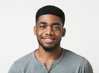 Young smiling african-american man over white background