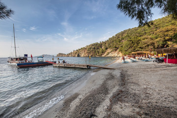 Fethiye, Turkey - October 21, 2018 : Help beach people doing vacation. Beach with surrounded by green trees.