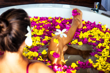 Back of woman in a bathtub with tropical exotic flowers in the water and flower white plumeria in her hair.girl in eco hotel taking bath in the spa salon summer vacation in a deluxe room ,skin care
