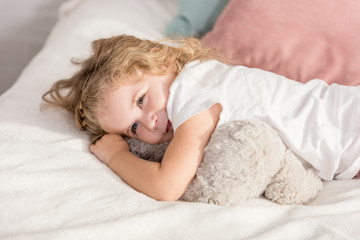 smiling adorable happy kid lying on bed in children room and looking away