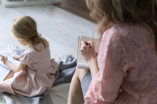 young mother and daughter both blondes sit back and write lists and goals for the new year. Mom writes with her left hand. Pink. Natural light. Without a face