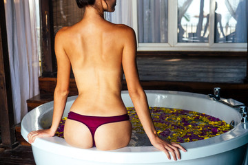 Attractive naked girl enjoys a bath with milk and pink yellow tropical flowers. Spa body care.beautiful woman in jacuzzi in bali in eco hotel relaxation massage procedures,a day for yourself pleasure