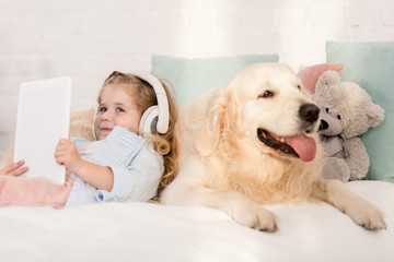 adorable kid listening music with tablet and leaning on golden retriever on bed in children room