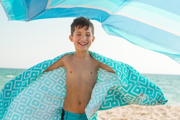 A cheerful kid on the beach wrapped in a bright beach towel.