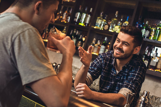 Young bartender standing at bar counter talking with customer drinking cocktail cheerful