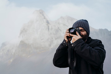 Anonymous tourist with camera against mountain in Iceland